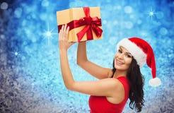 圣诞老人帽子的愉快的妇女有在闪烁的礼物的 免版税库存照片