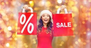 圣诞老人帽子的愉快的妇女有红色购物袋的 库存图片