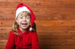 圣诞老人帽子的愉快的孩子在与拷贝空间的木背景 库存图片