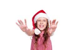 圣诞老人帽子的愉快的小女孩 免版税库存照片