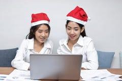 圣诞老人帽子的愉快的年轻亚裔女商人使用膝上型计算机在办公室 圣诞节或x-mas概念 免版税图库摄影