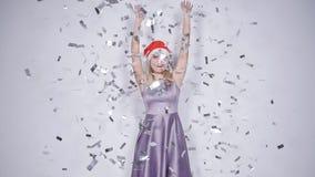圣诞老人帽子的愉快的年轻女人在与五彩纸屑落的庆祝党 影视素材
