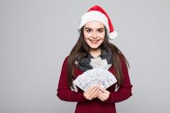 圣诞老人帽子的愉快的年轻微笑的妇女有在灰色背景隔绝的美金的 免版税库存图片