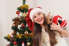 圣诞老人帽子的愉快的微笑的妇女有玩具狗的 免版税库存照片