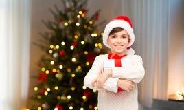 圣诞老人帽子的愉快的男孩有在圣诞节的礼物盒的 免版税库存图片