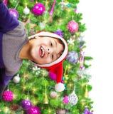 戴圣诞老人帽子的愉快的男孩 免版税库存图片