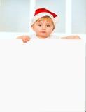 圣诞老人帽子的愉快的男婴有空白的委员会的 图库摄影