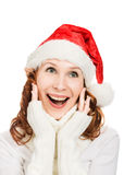 圣诞老人帽子的愉快的美丽的圣诞节妇女 免版税库存图片