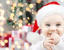 圣诞老人帽子的愉快的婴孩在圣诞灯 免版税图库摄影