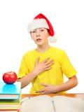 圣诞老人帽子的担心的男小学生 免版税库存照片