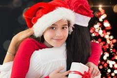 圣诞老人帽子的拥抱的母亲和女儿 免版税库存图片