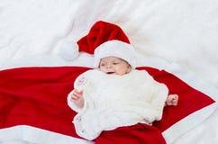圣诞老人帽子的新出生的圣诞节婴孩 库存图片