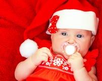 戴圣诞老人帽子的新出生的女孩 库存照片