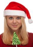 圣诞老人帽子的新白肤金发的妇女用糖果 免版税库存图片