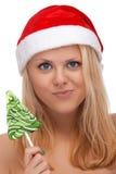 圣诞老人帽子的新白肤金发的妇女用糖果 免版税库存照片