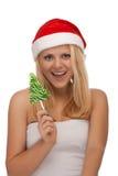 圣诞老人帽子的新白肤金发的妇女用糖果 免版税图库摄影