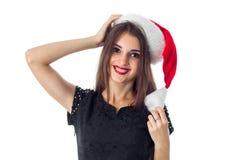 圣诞老人帽子的深色的女孩微笑在照相机的 免版税库存图片