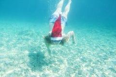 圣诞老人帽子的游泳的妇女在水面下 图库摄影