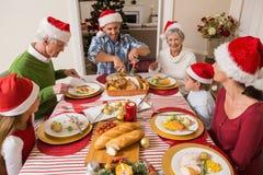 圣诞老人帽子的父亲雕刻烘烤火鸡的在圣诞节 免版税库存图片