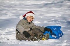 圣诞老人帽子的男孩在冬天步行在公园 库存图片