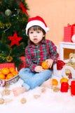 2年圣诞老人帽子的男孩在圣诞树附近坐 免版税库存照片