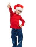 圣诞老人帽子的男孩有赞许标志的 免版税库存照片