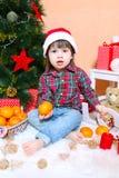 2年圣诞老人帽子的男孩用在圣诞树附近的蜜桔 免版税库存照片