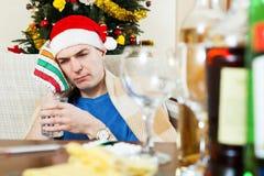 圣诞老人帽子的病的余醉未醒而难受的人有杯的水 免版税图库摄影