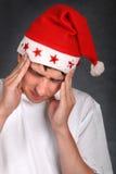 圣诞老人帽子的痛苦的少年 免版税图库摄影