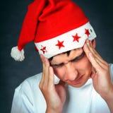 圣诞老人帽子的痛苦的少年 免版税库存图片