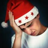 圣诞老人帽子的痛苦的少年 免版税库存照片