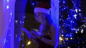 圣诞老人帽子的白肤金发的女孩有片剂的 股票视频