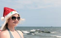 圣诞老人帽子的白肤金发的妇女在热带海滩 免版税库存照片