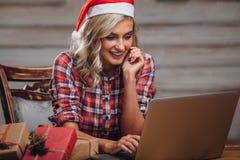 戴圣诞老人帽子的白肤金发的妇女,与膝上型计算机一起使用 免版税图库摄影