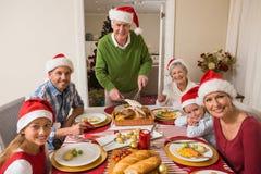 圣诞老人帽子的祖父雕刻烘烤火鸡的在圣诞晚餐 免版税库存照片