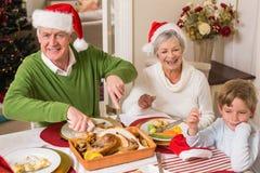 圣诞老人帽子的祖父雕刻烘烤火鸡的在圣诞节 库存图片