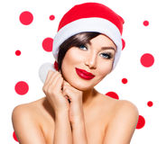 圣诞老人帽子的秀丽式样女孩 免版税库存图片