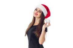 圣诞老人帽子的秀丽深色的女孩 库存图片