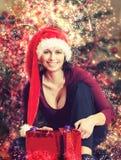 圣诞老人帽子的美丽的中年妇女在抽象backgroundCh 库存图片