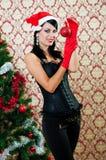 圣诞老人帽子的美丽的女孩在圣诞树附近 免版税图库摄影