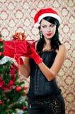 圣诞老人帽子的美丽的女孩在圣诞树附近 免版税库存图片