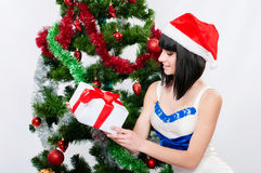 圣诞老人帽子的美丽的女孩在圣诞树附近 库存图片