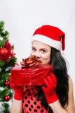 圣诞老人帽子的美丽的女孩在圣诞树附近 免版税库存照片