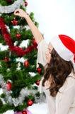 圣诞老人帽子的美丽的女孩在圣诞树附近 图库摄影