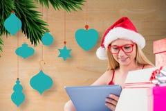 圣诞老人帽子的美丽的妇女使用数字式片剂 库存图片