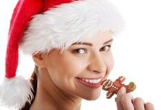圣诞老人帽子的美丽的妇女吃曲奇饼的。 库存图片