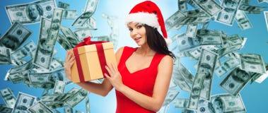 圣诞老人帽子的美丽的妇女有在金钱的礼物的 免版税库存照片