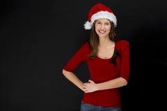 戴圣诞老人帽子的美丽的妇女 库存照片
