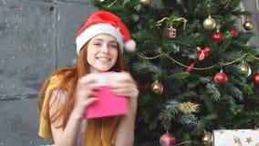 圣诞老人帽子的美丽的少妇庆祝圣诞节的拿着礼物盒 股票录像