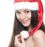 圣诞老人帽子的美丽的少妇 免版税图库摄影